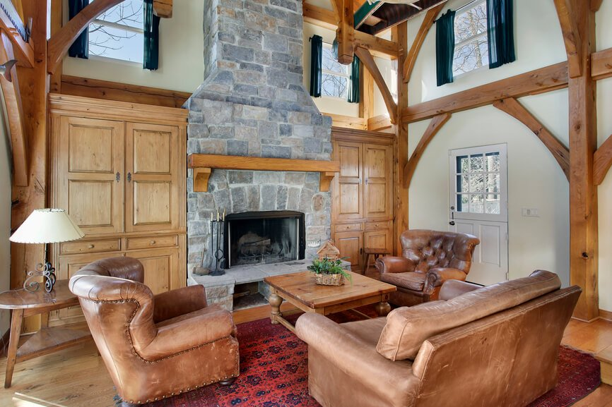 A beautiful rustic living room with pine built-ins on either side of the imposing mortar and stone fireplace. The wooden mantle matches the rest of the wood in the room.