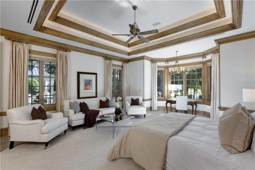 Perhaps the most stunning part of this room is the multiple tiers of tray ceilings with gorgeous hardwood crown molding. A small desk area is positioned in the bay window area, while a sofa and two chairs face the foot of the bed.