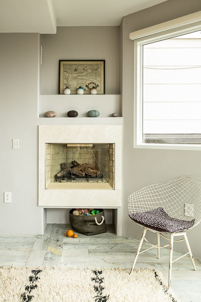 The primary bedroom features a small enclosed fireplace above a storage nook. Inset shelving above the fireplace draws the eye upwards.