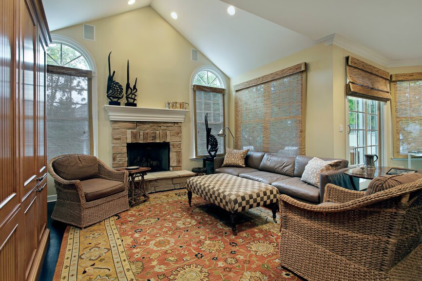 This eclectic living room features a small stone fireplace, wicker chairs paired with a leather sofa, and a checkerboard patterned ottoman. Natural fiber shades can be drawn over the numerous windows.