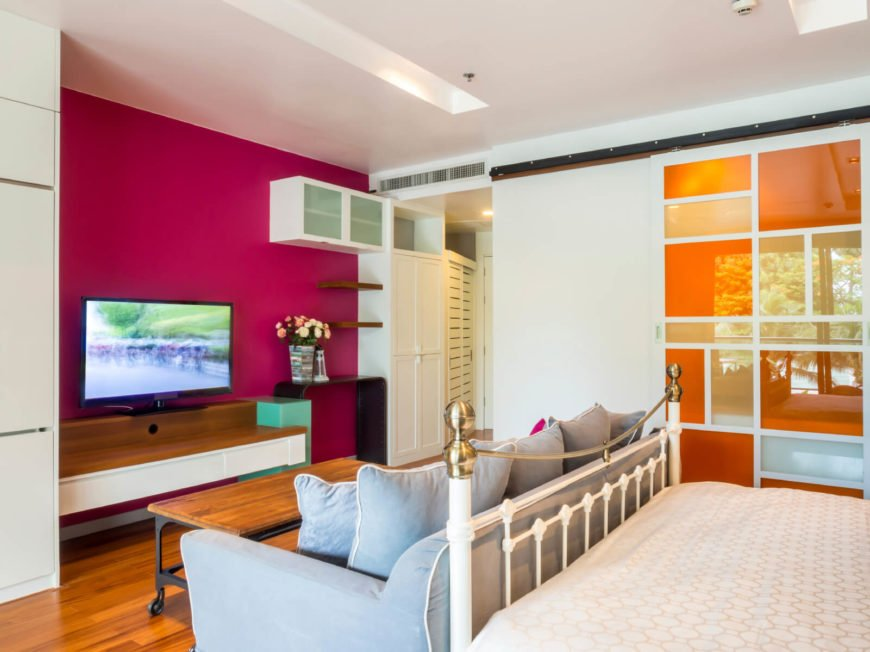 A modern-style bedroom that combines contemporary bold colors like berry and orange with vintage furniture, including a baby-blue sofa at the foot of the white wrought iron bed frame.