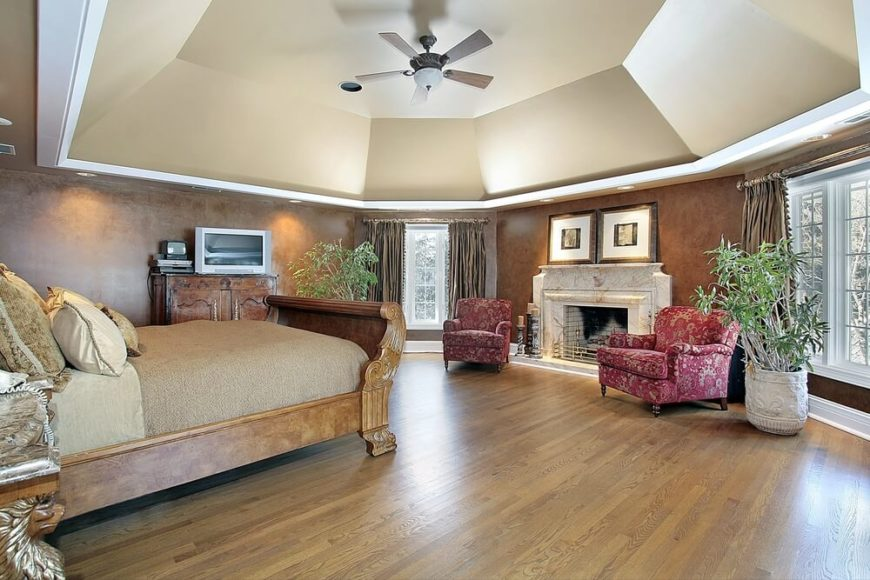 The eye is drawn upwards by the sheer depth of the tray ceiling. The ceiling is painted a light beige, which contrasts sharply with the textured dark brown of the walls