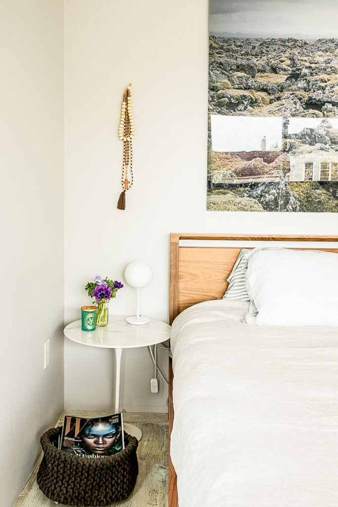 The bedside area of the primary bedroom continues the minimalist aspect of the hallways and the living room, the nightstand appearing to be simply a smaller version of the dining room table.
