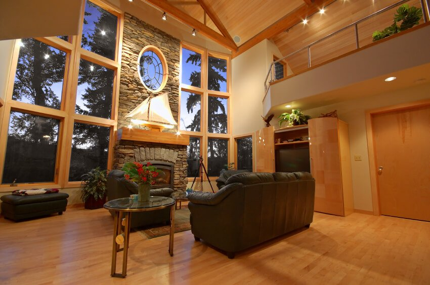 This living room has a large row of windows lining the front wall. The hardwood floors match the natural wood on the ceiling and window panes to create a wholesome country style.