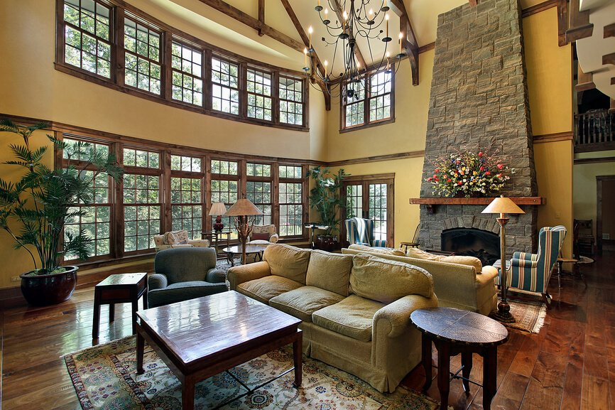 This cavernous living room is split into two different living room areas, each with a separate seating arrangement. The stone fireplace continues all the way up to the ceiling, tapering slightly. Two rows of windows let in ample natural light.