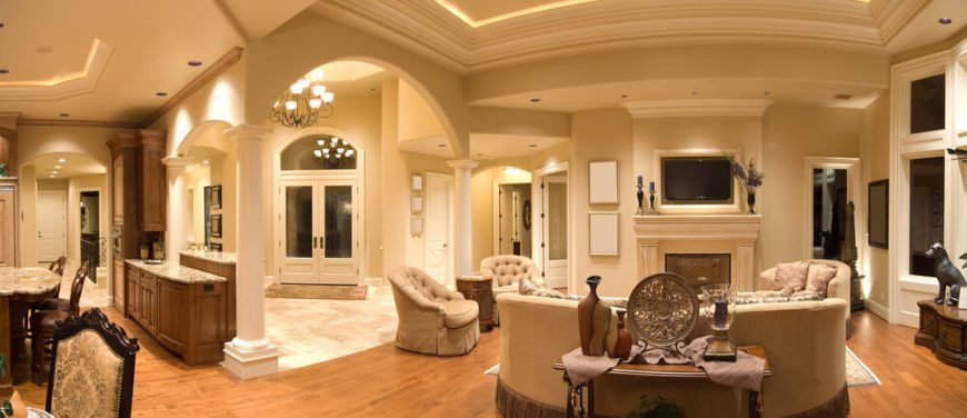 This luxurious living room holds a lot of different shapes and designs. The hardwood flooring keeps the consistency of the colors within the walls and chairs.