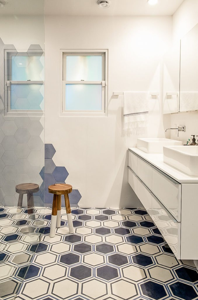 The primary bathroom introduces a new concept in the home: a repeating geometric pattern. The room is separated into a wet room and dry room via a glass shower enclosure.