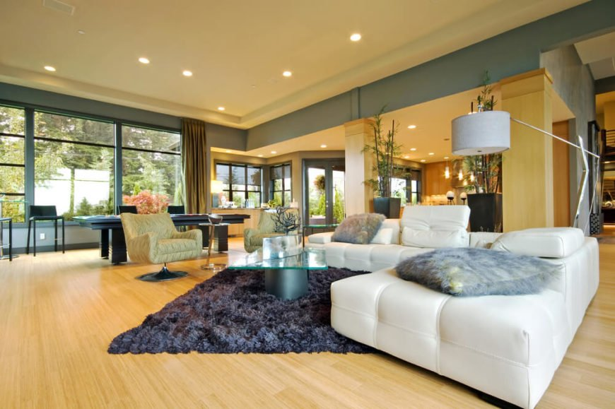 There are a lot of different colors in this living room. From white to a bluish-grey, the blonde hardwood flooring does not take away from the accents of the room, but it complements them.