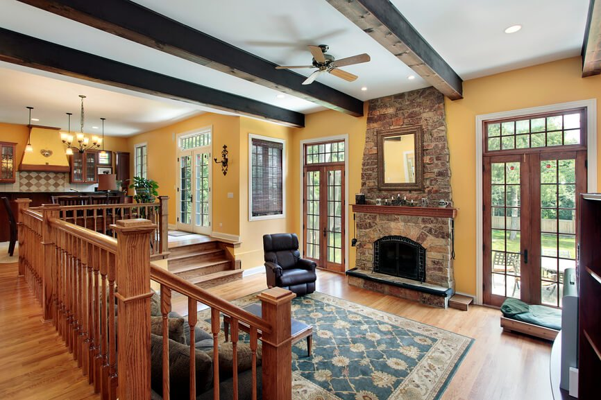 A pit living room with a large brick fireplace topped by a small wooden mantle and a gilded mirror. Doors on either side lead out onto the patio.