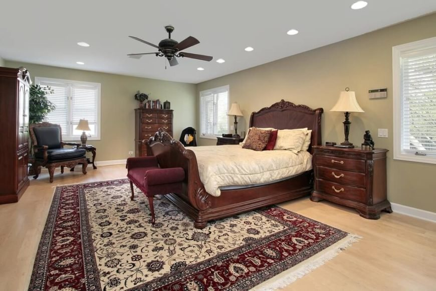 The ornate carving on the all-wood sleigh bed sets the tone for this elegant, spacious bedroom. The red of the settee draws inspiration from the red border of the area rug.