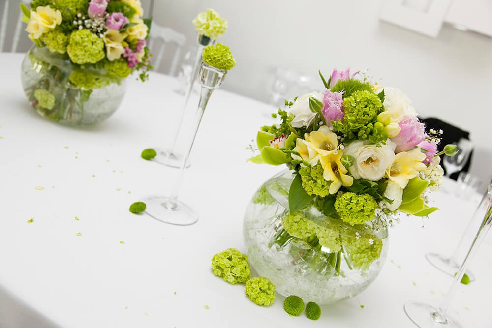 A globe-like glass vase is host to a number of light green hydrangea blooms, white roses, pale yellow lilies, and a few other lavender blooms.