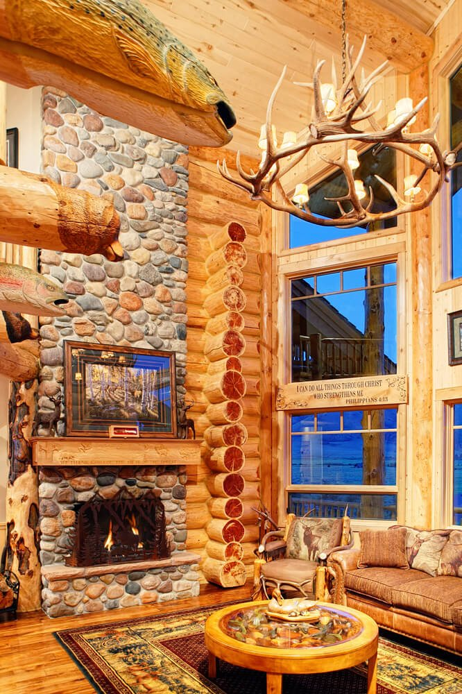 A rustic log cabin with a custom glass-topped display coffee table and an armchair decorated with sections of antler. The stone fireplace has an ornately carved mantle that matches the carved section between the windows.