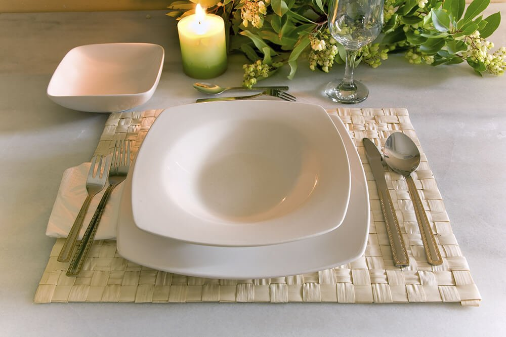 A contemporary white and cream table setting in a formal style with a woven mat and a small bowl off to the left.