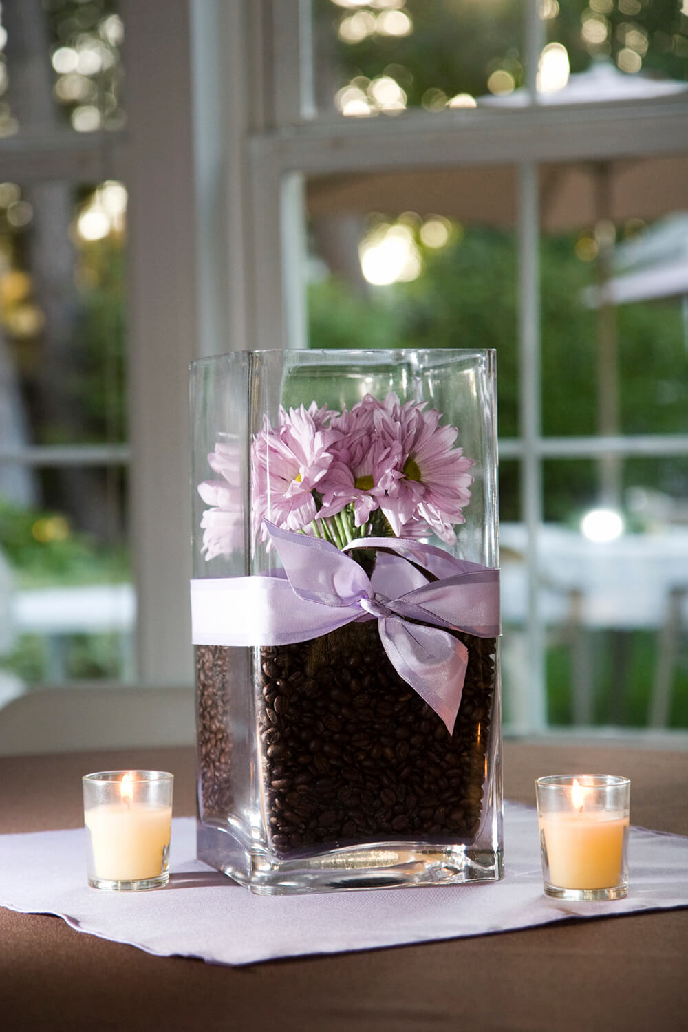 This take on a floral arrangement places a small bouquet of lavender daisies tucked into coffee beans. The flowers don't quiet reach the top of the vase, which is wrapped in a pastel ribbon. As the candles next to the vase warm, the coffee beans will start giving off a fragrant scent.