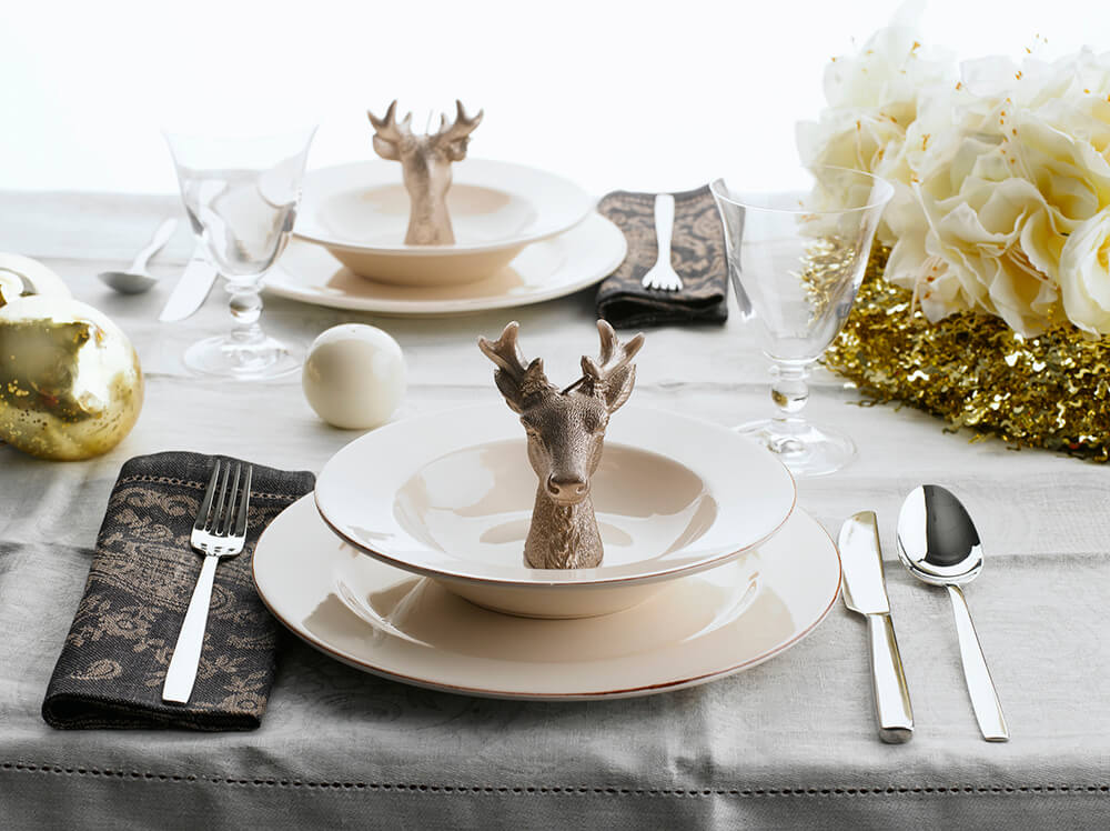 Following the trend of faux deer heads in decorating, this holiday table setting places one in each bowl. The centerpiece is soft floral textures on a bold shimmering gold base.