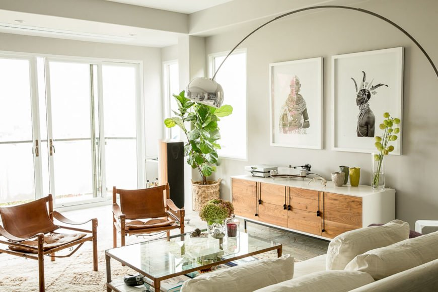 Upon entry to the home we are met by the open-concept main floor living space, which is enshrouded in white and natural wood. Arching floor lamps can be rotated to suit the needs of whomever is sitting on the linen sofa.