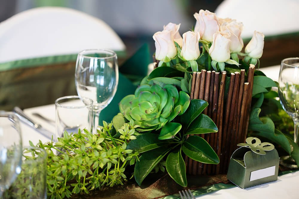 A longer floral arrangement with a base of succulents leading up into a vase of white rosebuds. The taller vase portion is surrounded by thin sticks.