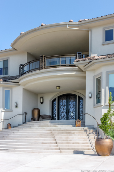 As we move towards the front door, we are greeted by a curved set of stairs leading up to the grand double doors. The doors feature more of the scrollwork from the fence. The pattern on the fence also matches the balustrade of the curved balcony above the doors.