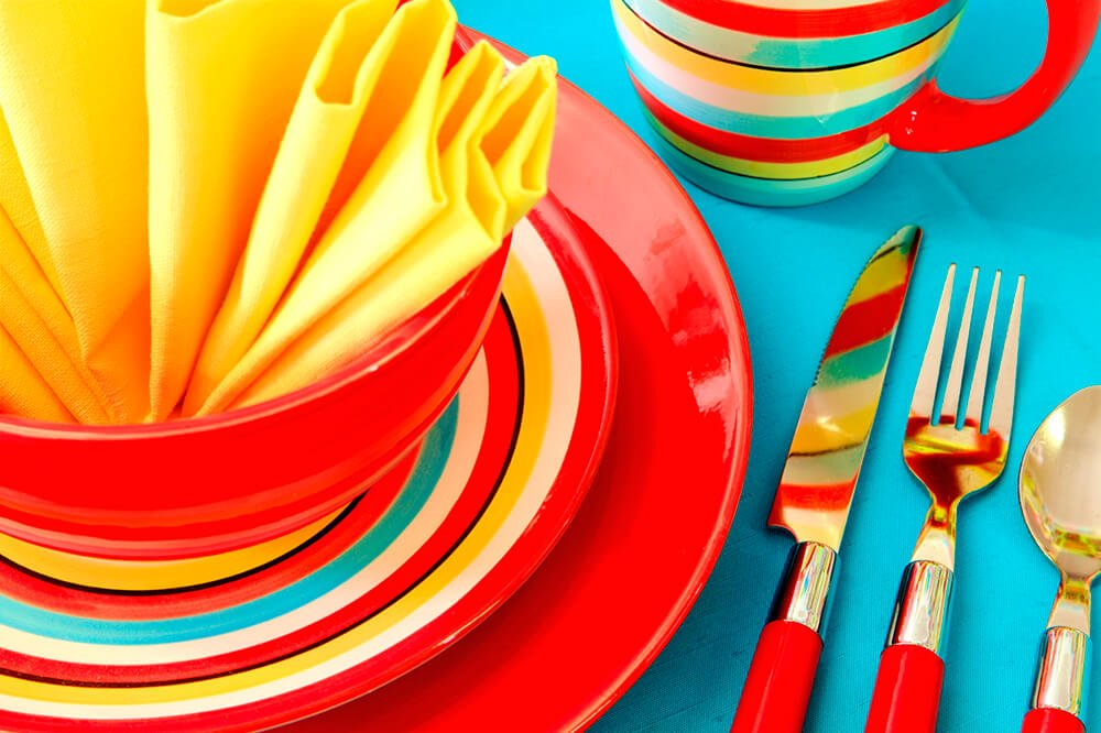 A bright and summery place setting in red, yellow, and blue. A fun folded napkin is placed into the bowl at the center of the arrangement.