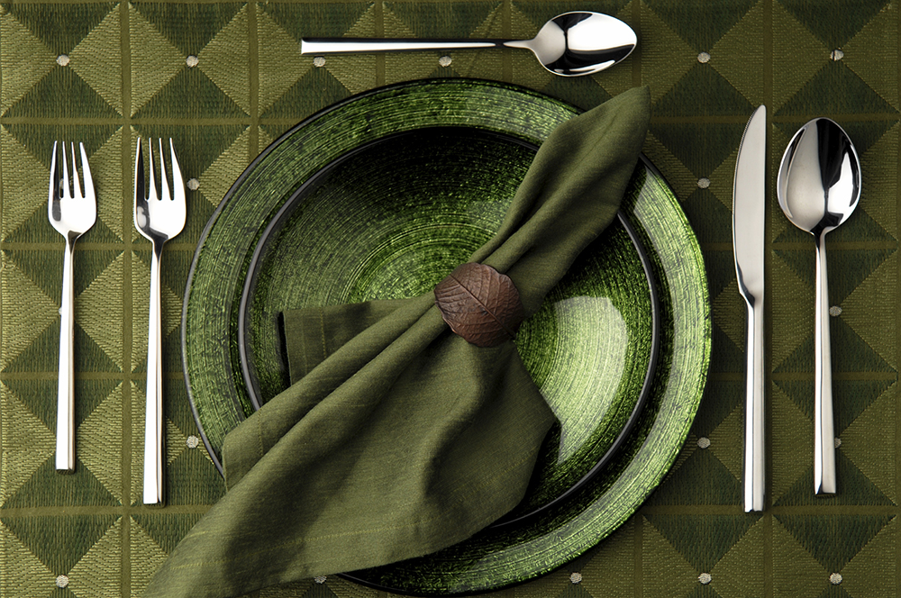 A table setting for one all in green with a simple brown leaf-shaped napkin ring.