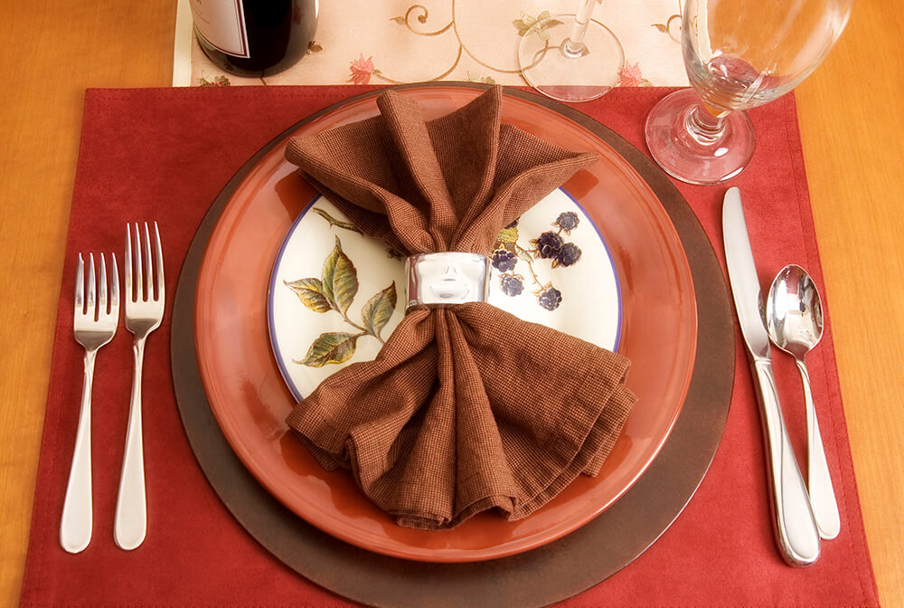 A red and brown table setting with a silver napkin ring. The bread plate at the center has a sprig of blackberries painted on it.