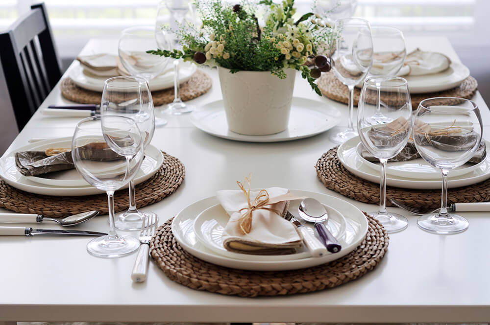 The woven wicker placemats help distinguish the glossy white plates from the matte white dining table. The two wine glasses are slightly different shaped.