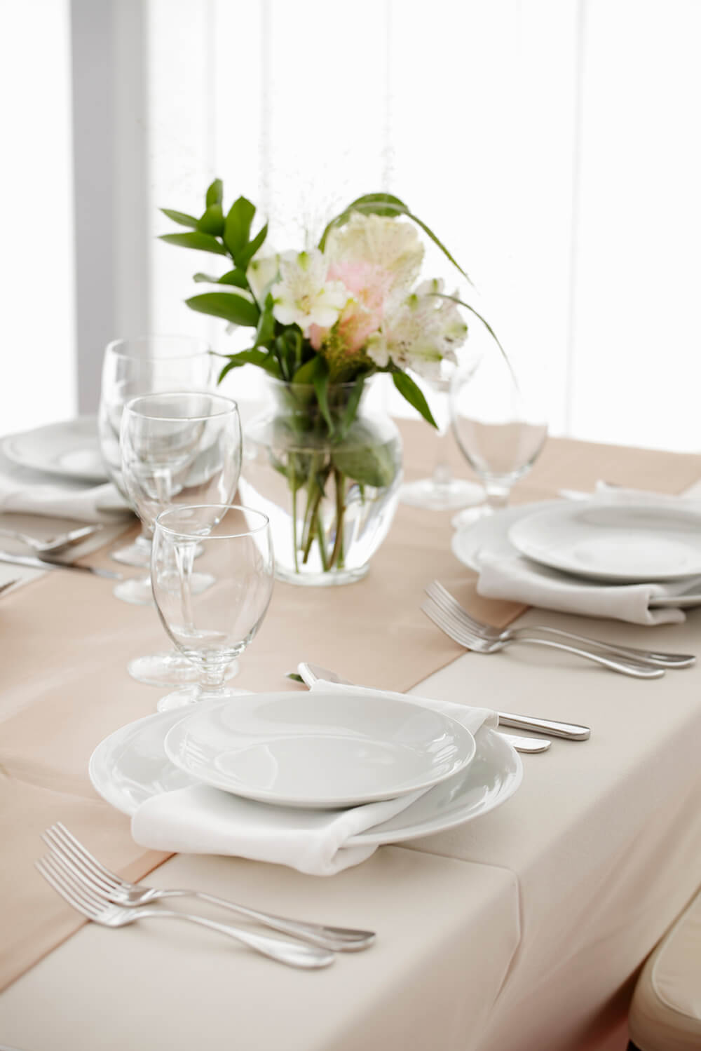 An off-white runner is layered on top of the white tablecloth. The slight change in color keeps this all white arrangement from blending together.