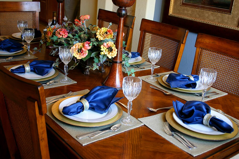 Bold sapphire blue napkins lay on white salad plates atop golden dinner plates. The placemats are a light silvery-gray.