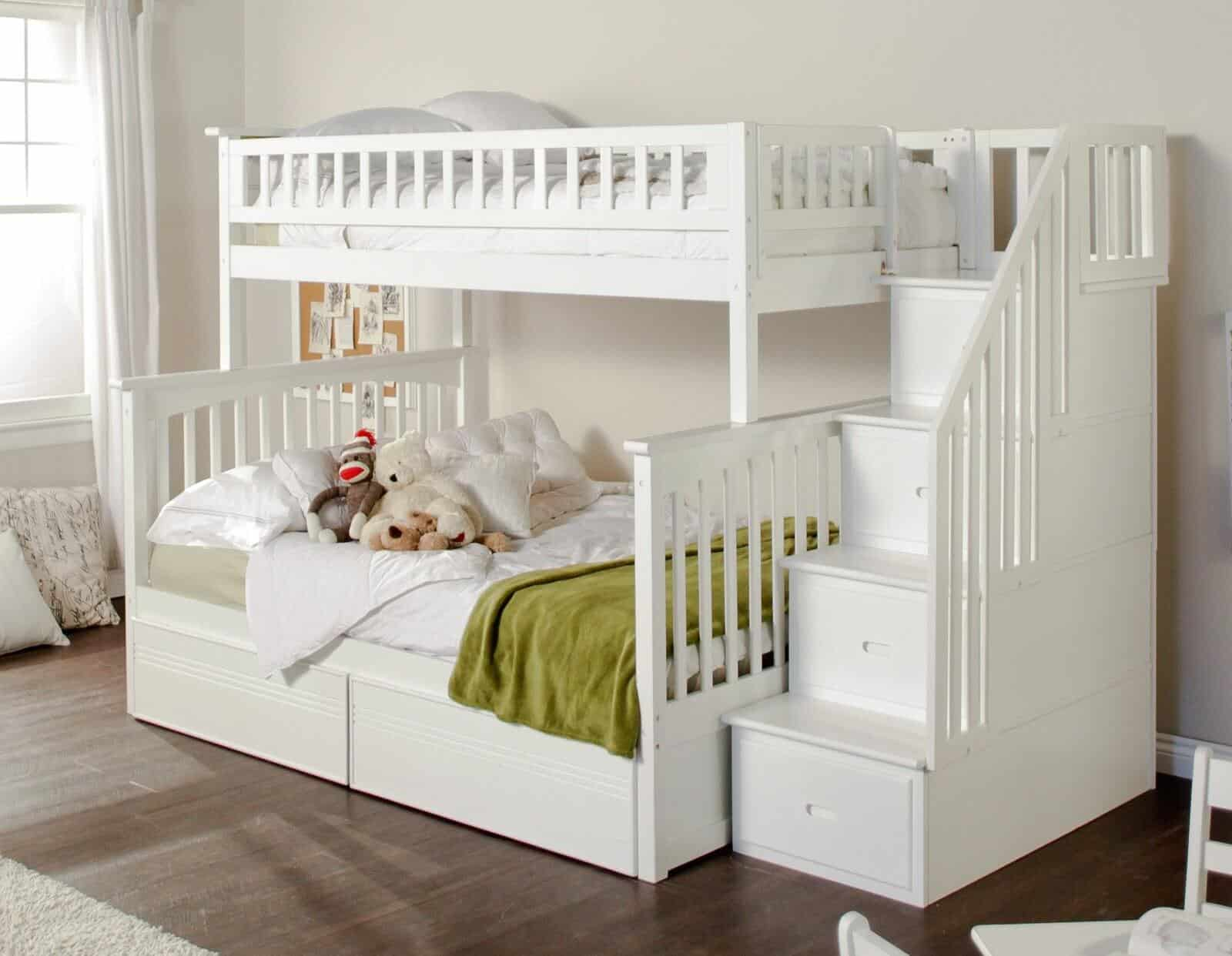 This pristine white painted bunk bed features a large full size lower bunk, with hidden storage below. Staircase on right side features built-in drawers.