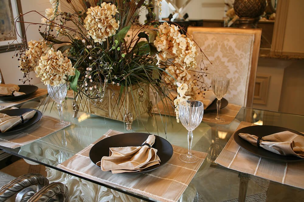 A cream and brown informal setting on a glass-top table. The dining chairs around the table have ornate carvings.