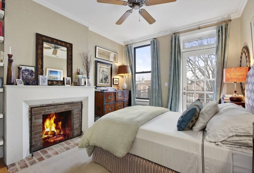 A smaller primary bedroom with a brick fireplace and a door leading out onto a deck. The room also features a small wooden ceiling fan above the bed.