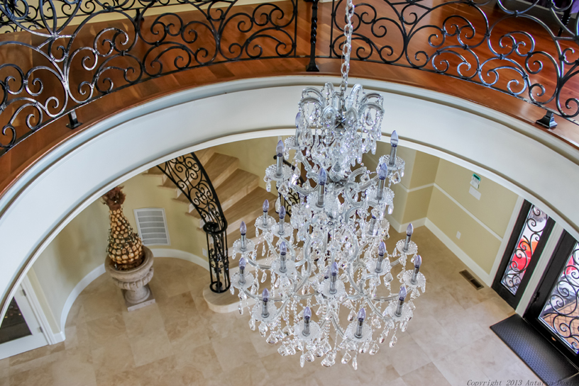 Here we are viewing the entrance to the home from the top of the staircase. The chandelier is hung at the perfect height to provide light to both levels of the foyer.