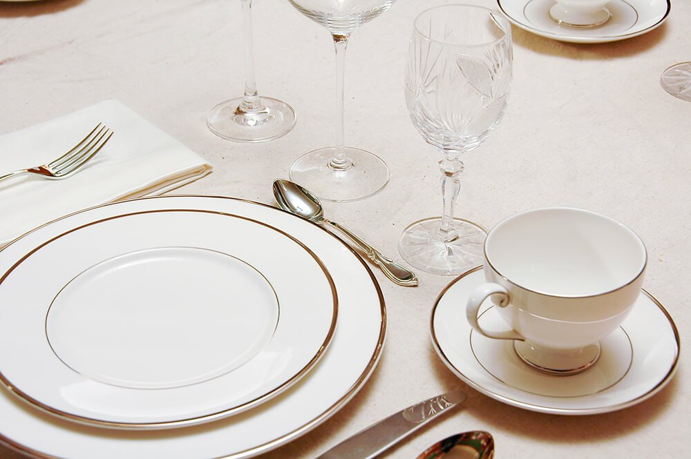 A simple but elegant table setting in white with silver-rimmed dishes. Each wine glass is crystal with a delicate pattern.