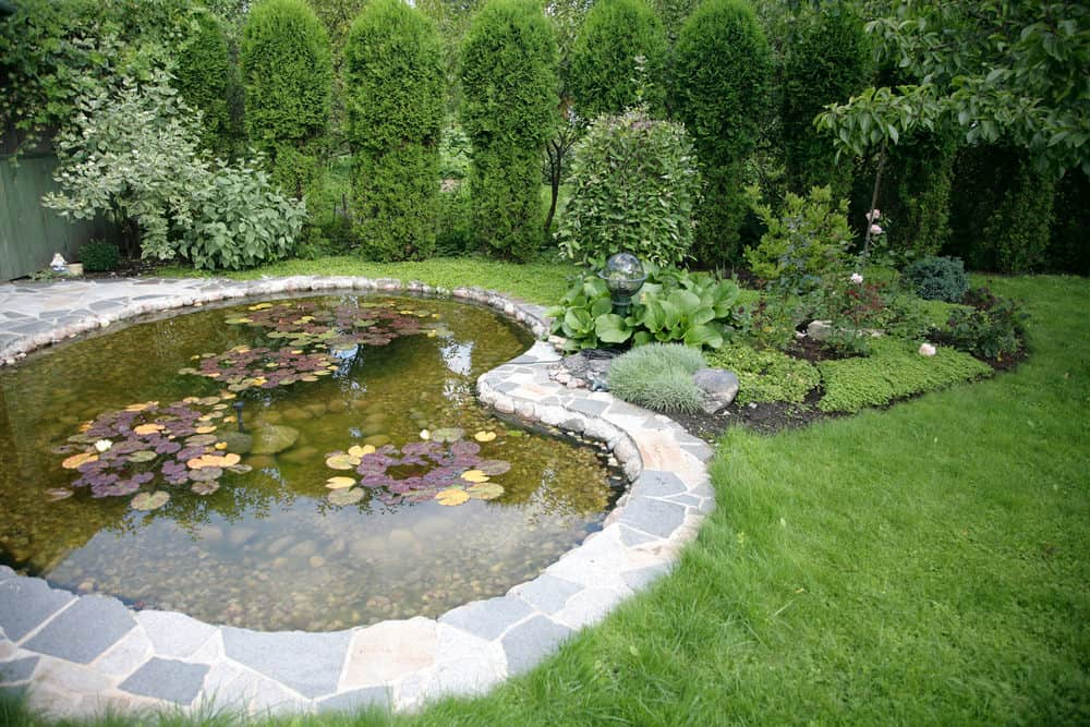 This heart shaped pond is framed in uneven paver rocks in pastel colors. A small garden to the side is a nice additions.