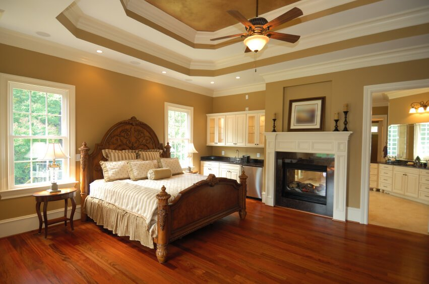 An elegant primary bedroom with rich red hardwood floors, a dual-sided fireplace shared with the primary bathroom, and even a small kitchenette in a nook. The ceiling fan sits at the center of a 3 tiered tray ceiling.