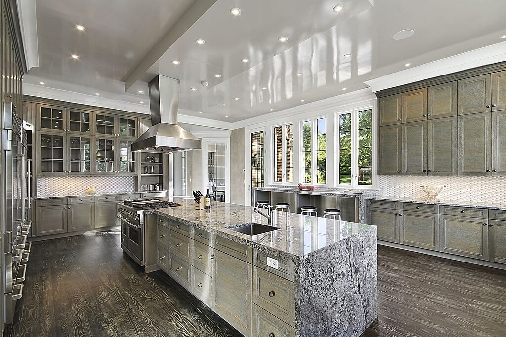 Fantastic English styled windows sit amidst the bar for a delightful addition to this remarkable kitchen. This impressive modern design has colonial glass cabinet doors and a striking marble finish to the countertop. The floor and cabinets are wooden with a unique two-toned grey color scheme.