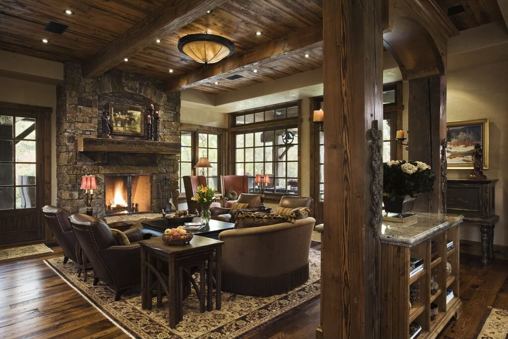 A rustic yet elegant living room in wood and stone. The wood-burning fireplace is screened to avoid any cinders escaping and causing a fire hazard.