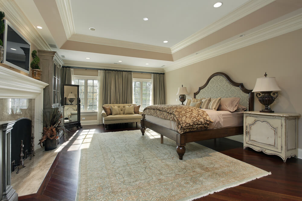 A spacious bedroom with hardwood floors and a stately fireplace. Two large windows are inset behind a tufted loveseat to the rear of the room.