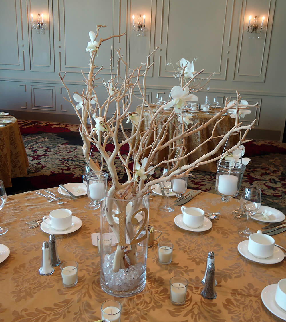 To create this centerpiece, a tall glass vase's is bottom is filled with an inch or so of crystals. Branches are tucked into the crystals and small votive candles are suspended from the branches alongside the delicate blossoms.