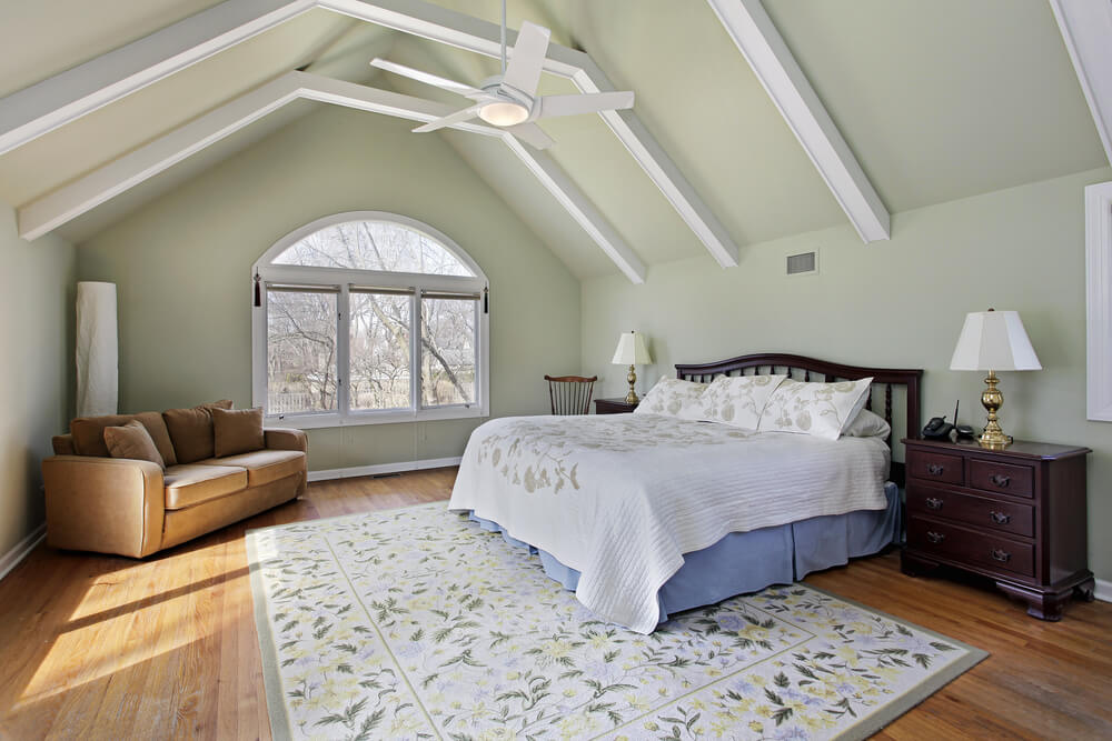 A simple, charming attic bedroom with exposed rafters painted white and a single loveseat in the cornet next to the expansive window.