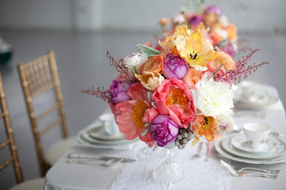 A crystal holder topped with an eclectic bouquet of large-bloom flowers in lovely pastels.