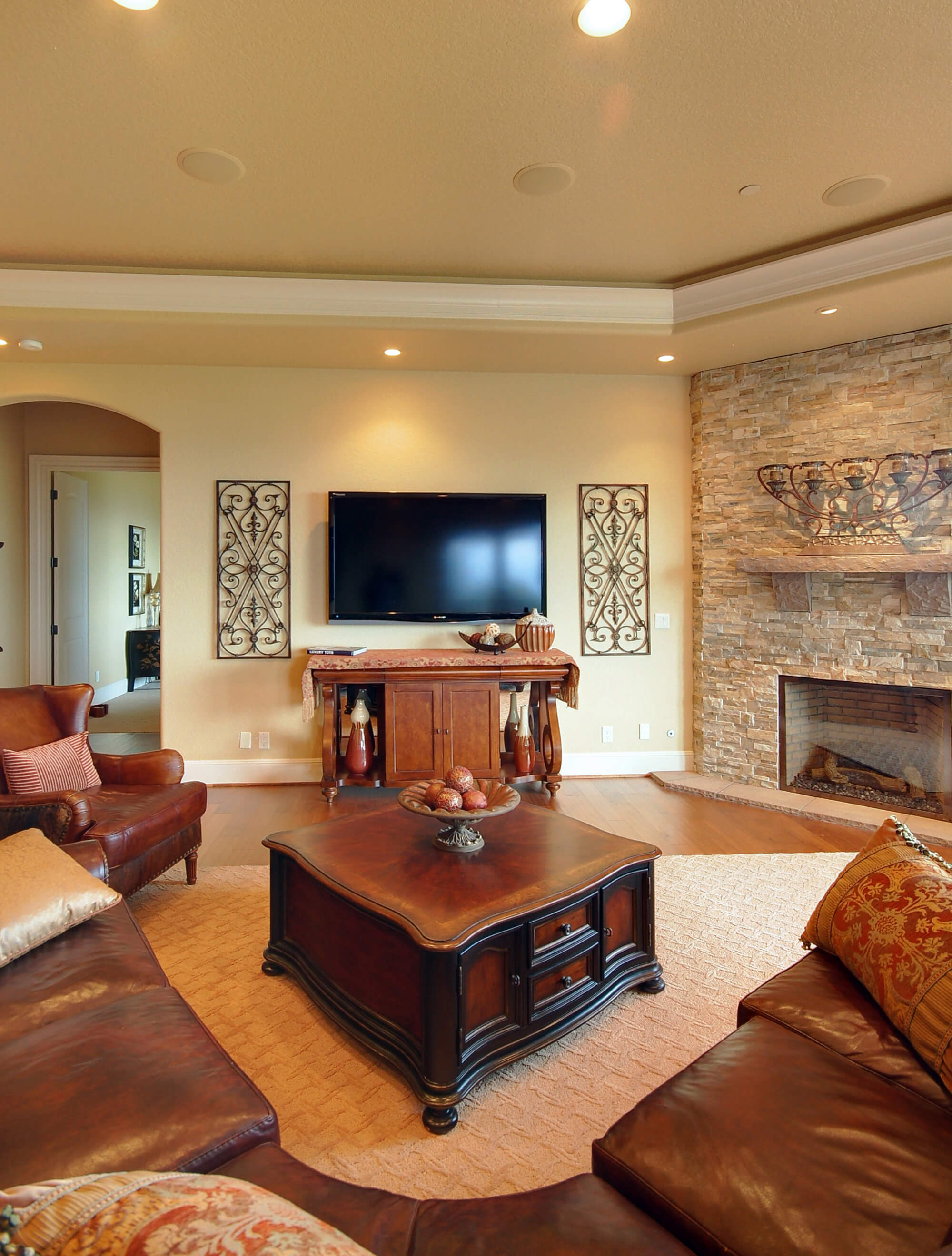 This southwestern style living room has a corner fireplace with an enclosed hearth and a rustic wooden mantle. The stone facade is small stone tiles.