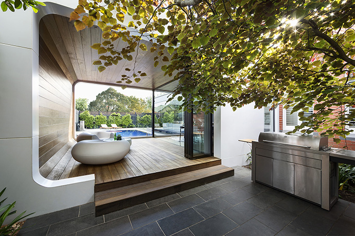 A 3-seasons room sits behind the house, attracting attention with its incredible round walls and natural wood. The glossy white of the walls contrasts with the dark wood that curls from the floor and up onto the ceiling.