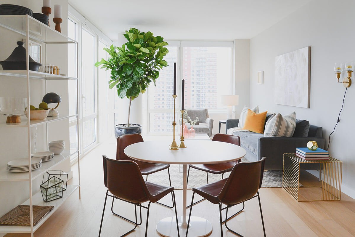 The home centers on an open-plan space including this dining area and family room. Full height windows surround for an open, bright interior.