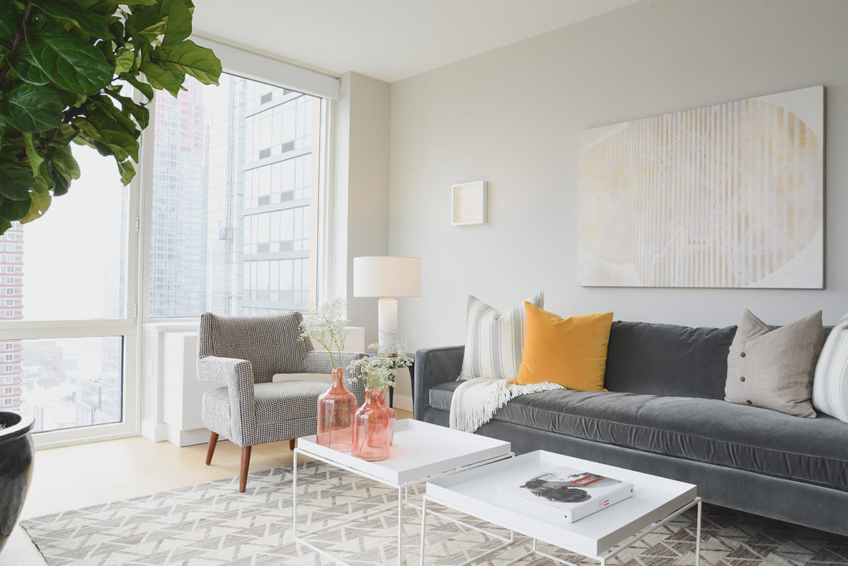 A lot of high detail texture goes into this room, from the patterned area rug to the bespoke armchair in front of the window. The unfussy contemporary styled furniture makes for a subtly modern look.