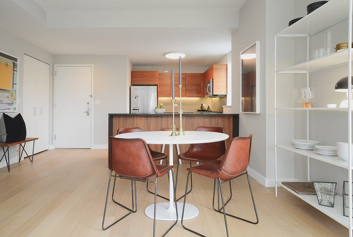 Turning around, we see the kitchen across from the open dining area. The dining table itself is a circular white design, surrounded by leather upholstered wire frame chairs.