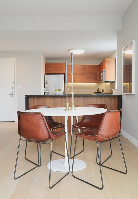 The kitchen boasts rich natural wood tones across all cabinetry, adding an organic contrast to the sleek white surroundings. The hardwood flooring appears in a much lighter tone.
