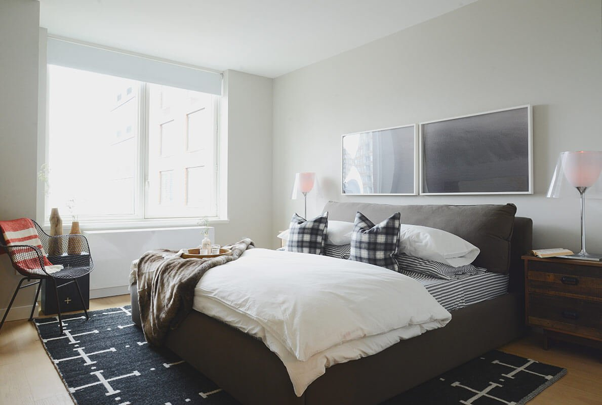 The primary bedroom, also wrapped in white with light hardwood flooring, centers on a large leather upholstered bed in grey. A black and white patterned area rug fills the middle of the space, while rustic styled bedside dressers provide utility and storage.