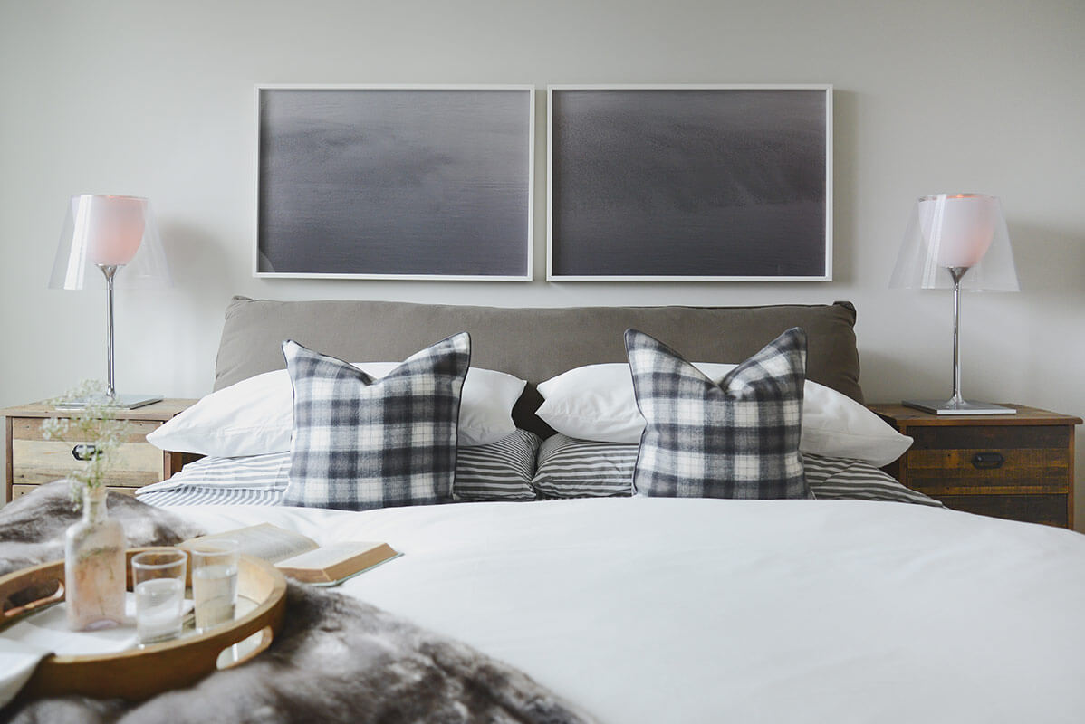 In lieu of a traditional headboard, the primary bedroom sports this dual pane of framed black stained wood, adding a stark contrast to the white walls.