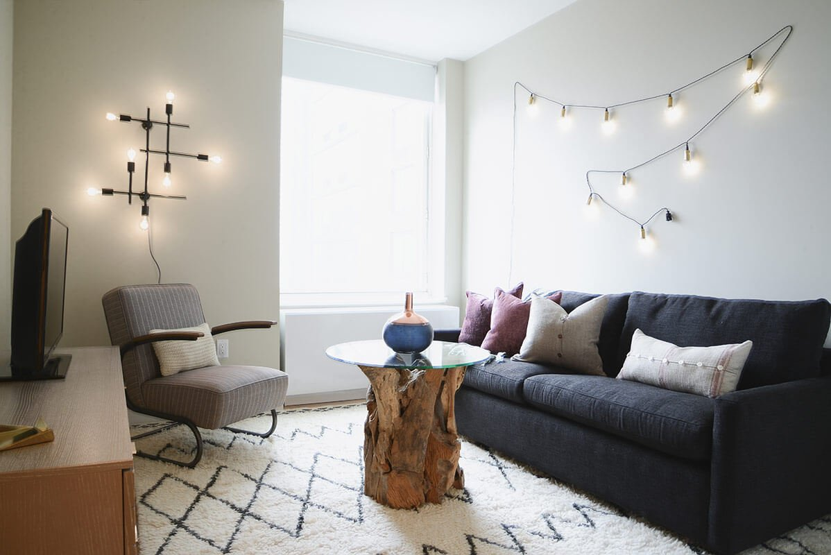 The media room, converted from a former bedroom, centers on an intriguing coffee table crafted of glass and knotty found wood. The sofa converts into a bed for when guests or children arrive.